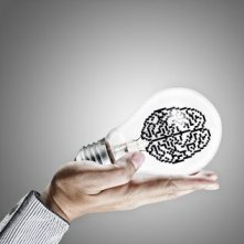 hand shows 3d pixel icon brain in light bulb as concept